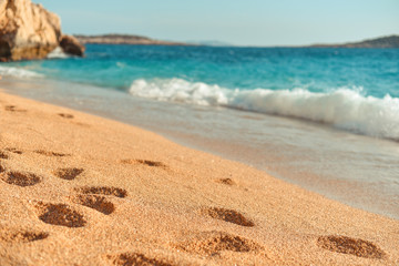 Footprints from people on the azure beach. Concept of relaxing on sea coast in summer. Beach of Kaputas, Turkey