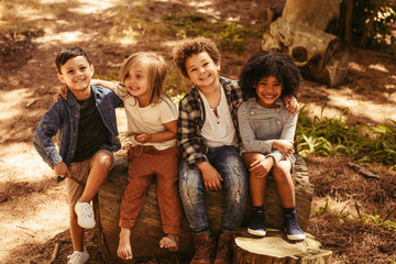 Group of kids on a wooden log