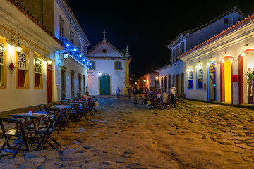 Fotomurales - Night view of street of historical center with tables of restaurant in Paraty, Rio de Janeiro, Brazil. Paraty is a preserved Portuguese colonial and Brazilian Imperial municipality