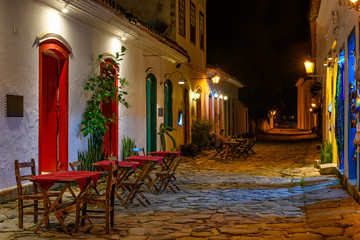 Wall Mural - Night view of street of historical center with tables of restaurant in Paraty, Rio de Janeiro, Brazil. Paraty is a preserved Portuguese colonial and Brazilian Imperial municipality