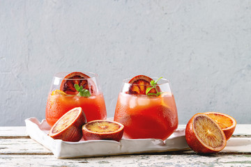 Blood orange iced cocktails in glasses, decorated by slice of oranges and fresh mint, served in ceramic tray on white wooden table with grey wall at background.