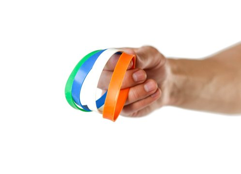 Colored rubber bracelets on the arm. Close up. Isolated on white background