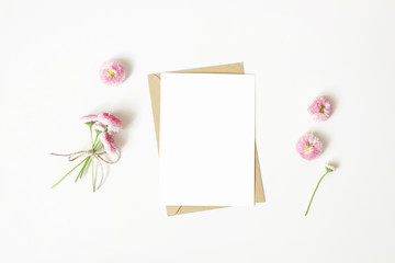 Feminine stationery, desktop mock-up scene. Vertical blank greeting card, craft paper envelope and daisy bouquet and flowers isolated on white table background. Flat lay, top view. Rustic composition.