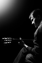 black and white portrait of asian musician playing acoustic guitar on stage