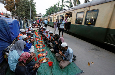 Muslim men pray as they sit before their iftar (breaking of fast) meal next to a train passing on a railway platform during the holy fasting month of Ramadan, in Kolkata