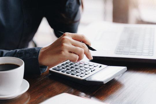 Woman entrepreneur using a calculator to calculating financial expense at coffee shop.