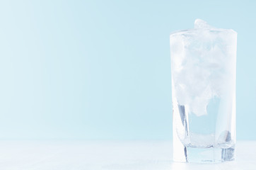 Cold water with ice in misted drinking glass on soft light blue background, white wood board.