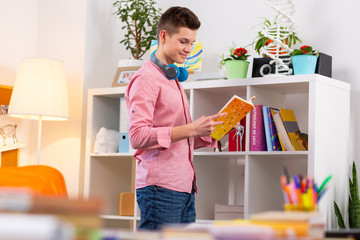 Student standing near bookcase and choosing the book to read