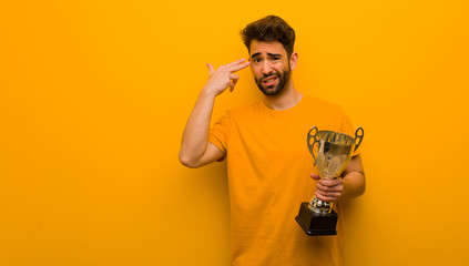Young man holding a trophy doing a suicide gesture Wall mural