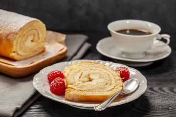 Ciasto - rolada biszkoptowa z kremem mascarpone na talerzyku, obok kawa w filiżance, wszystko postawione na czarnym drewnianym blacie