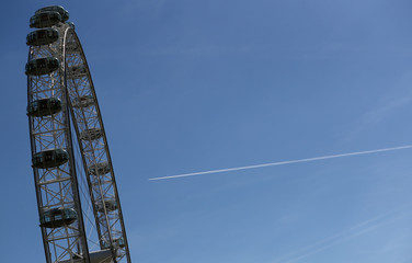 An airplane leaves a vapour trail as it flies past the London Eye in London