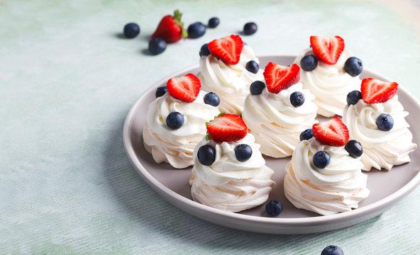 Mini Pavlova meringue with whipped cream and berries.