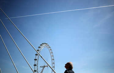 A man looks at an airplane leaving a vapour trail as it flies over the London Eye in London
