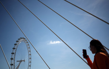 A woman photographs the London Eye in London
