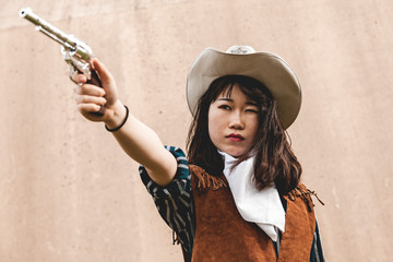 Portrait of a beautiful Chinese female cowgirl shooting with a gun