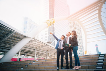 Portrait of businessteam pointing up the future on blurred city background. Business success concept
