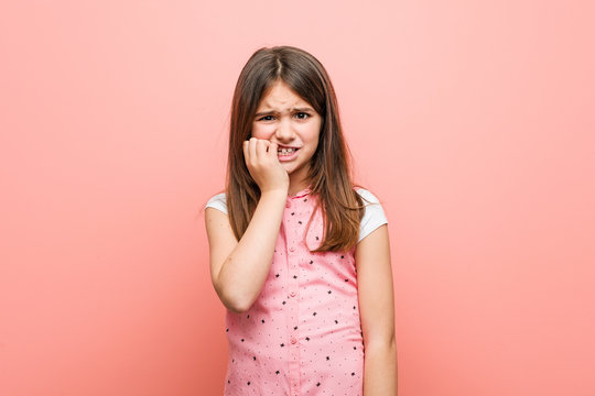 Cute little girl biting fingernails, nervous and very anxious.