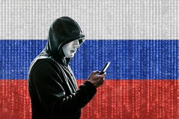 Russian hooded hacker with mask holding smartphone