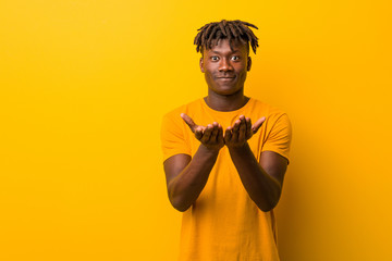 Young black man wearing rastas over yellow background holding something with palms, offering to camera. Wall mural
