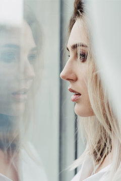 Beautiful woman looking out of the window in which her face is reflecting