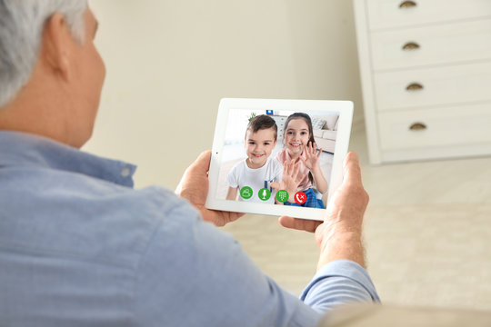 Closeup view of senior man talking with grandchildren via video chat at home