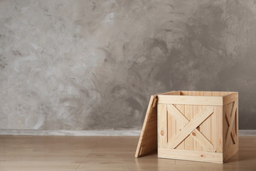 Wooden crate on floor against color background, space for text Wall mural