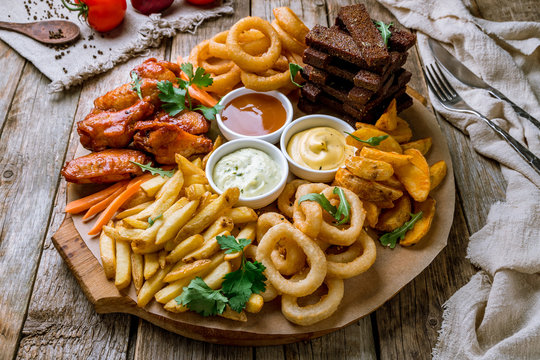 assorted beer snacks. Onion rings, chicken wings, french fries, and sauses