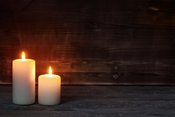 Burning candle on old wooden background