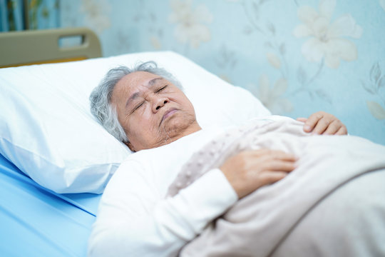 Asian senior or elderly old lady woman patient smile bright face with strong health while lying on bed in nursing hospital ward : healthy strong medical concept