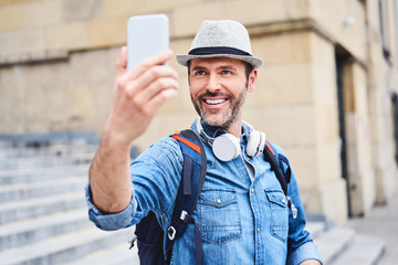 Tourist taking selfie with smartphone while sightseeing in the city Fototapete