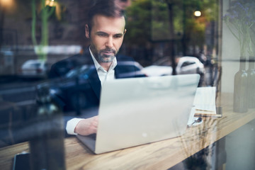 Handsome businessman working on laptop and sitting in cafe