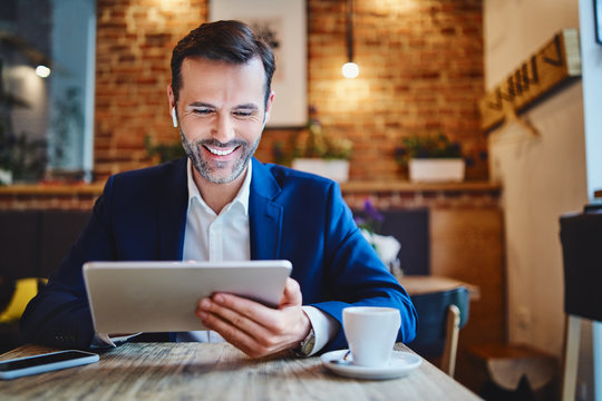 Portrait of businessman with wireless headphones using tablet in cafe