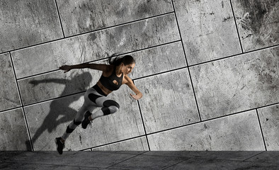Woman running on sidewalk. Urban background