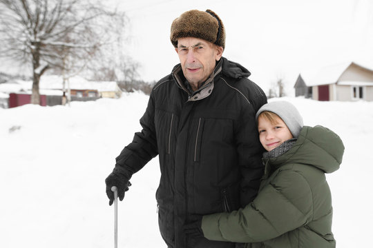 Portrait of grandfather and happy grandson in winter