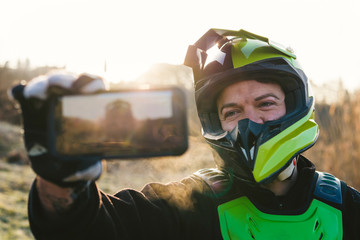 Portrait of motocross driver taking a selfie at sunset