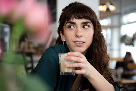 Portrait of young woman in a cafe looking around