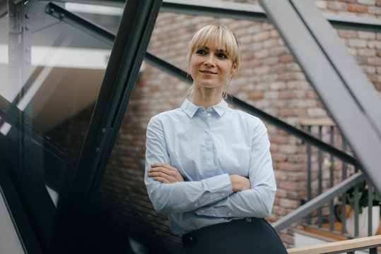 Confident woman sitting in office building with arms crossed