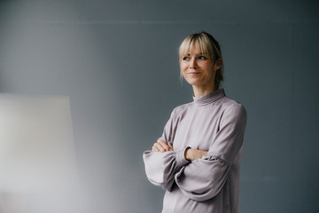 Portrait of a confident blond woman with arms crossed