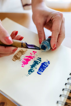 Woman's hand applying color pigments at coloring book