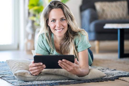 Portrait of smiling woman lying on the floor at home using tablet