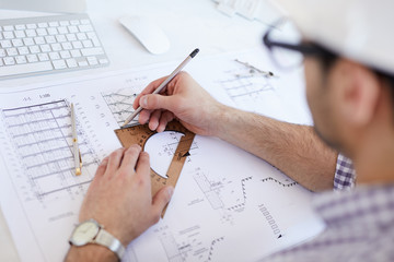 High angle view at engineer drawing plans and making measurements at workplace, copy space