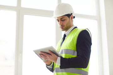 Waist up portrait of  Middle-Eastern engineer wearing hardhat standing against window  holding tablet, copy space