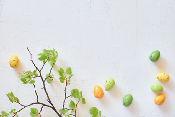 Fresh spring lime leaves and Easter eggs. Flat lay on textured white background, copy-space