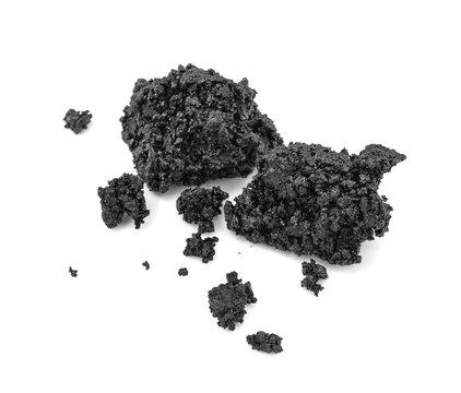 Piece of fresh asphalt isolated on white background. Pile of black raw asphalt.