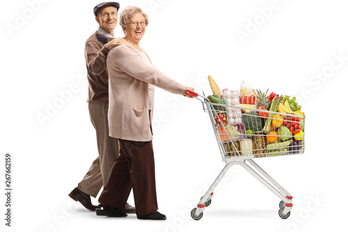 Elderly Couple Walking And Pushing A Shopping Cart With Food