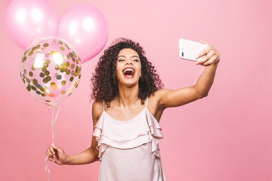 Self portrait of afro american positive girl in dress having balloons in hand shooting selfie on front camera isolated on pink background.