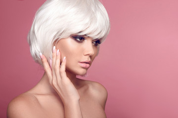 Blond bob short hairstyle. Makeup. Ombre manicure nails. Beautiful hair coloring woman. Trendy haircuts. Blonde model with short shiny hairstyle solated on pink studio background. Beauty Salon.