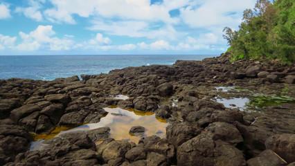 Rocky coast, water pools and blue pacific ocean at Queen's Bath, Kauai, Hawaii, USA