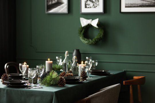 Christmas garland and black and white posters on green wall of dining room set for christmas dinner