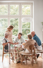 Elderly friends spending time together by drinking tea and enjoying photos in common dining room of...